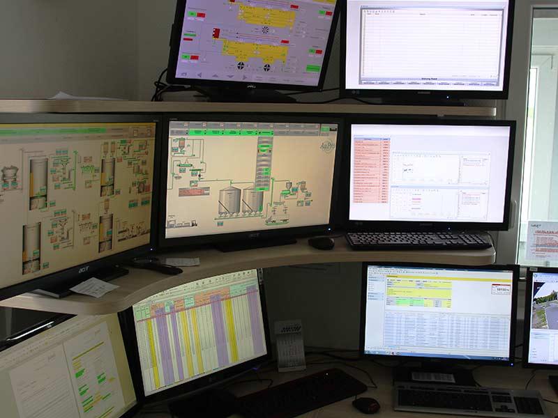 Mehrere Computerbildschirme im Kontrollraum des Holzpelletwerks
